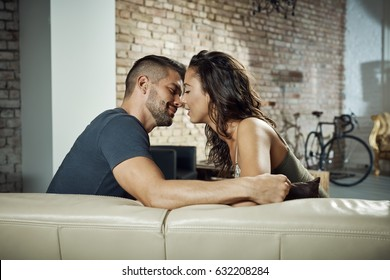 Beautiful young loving couple kissing at home on sofa.