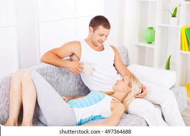 Beautiful young loving couple on a sofa. Wife is laying in husband's lap.