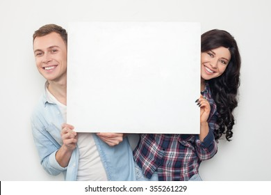 Beautiful young loving couple is showing a white empty placard to the camera. They are hiding behind it and smiling. Isolated