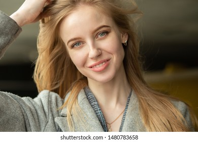 beautiful young luxury woman with long blond hair looking at camera smiling