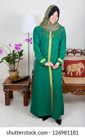 Beautiful young Malay woman in green suit, a traditional costume.