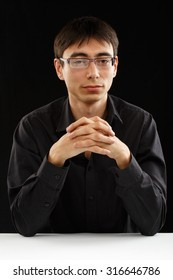 Beautiful young man in black shirt and glasses sitting at the table in thoughtful pose isolated on black background