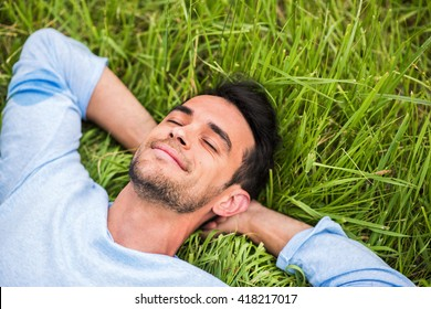 Beautiful young man with closed eyes, dreaming and relax on the green grass