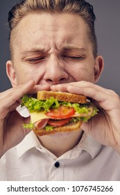 Beautiful Young man eating a fresh burger