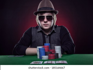 Beautiful young man on a beautiful background playing poker. Good luck in card games on the big money