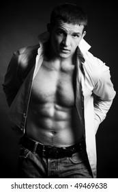 Beautiful young man posing on dark background