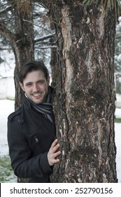 Beautiful young man smiling and hiding behind a tree