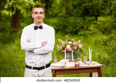 Beautiful young man standing near the elegantly served table with a bouquet, glasses, dishes. He looks happy.
