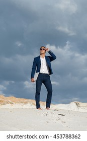 Beautiful young man in suit stands on top of hill sand  while in desert with laptop enjoying nature and the sun. Peaceful place to work and leisure. Achieving success