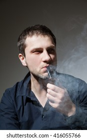 Beautiful young man with tobacco pipe, gray background