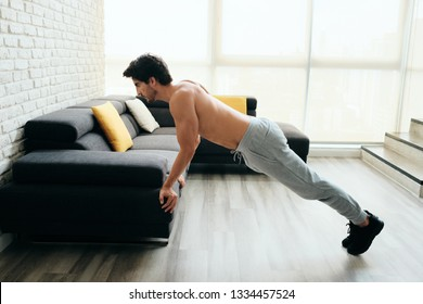 Beautiful young man training and working out. Athlete exercising with a chest routine for wellness in his living room. Latino people doing push-ups with backward grip using sofa at home.