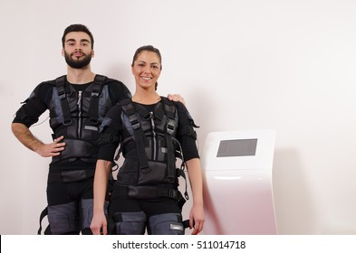 Beautiful young man and woman in suits for electro muscle stimulation EMS. Selective focus on man
