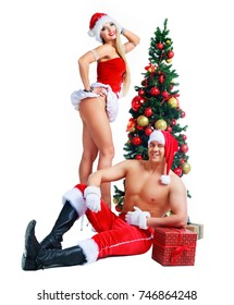 beautiful young man and woman wearing Santa's clothes with Christmas tree in the studio