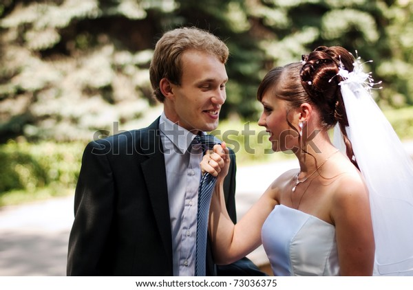 Beautiful and young married couple in the park, wife caught her husband for a tie