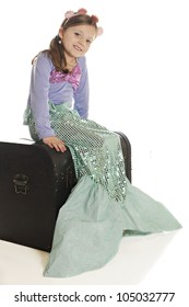 A beautiful young mermaid happily sitting on an old treasure chest.  On a white background.