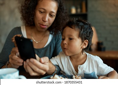 Beautiful young mixed race female freelancer working from home using mobile, her cute little boy taking cell phone from her, wants to watch cartoons during breakfast. Family, motherhood and technology