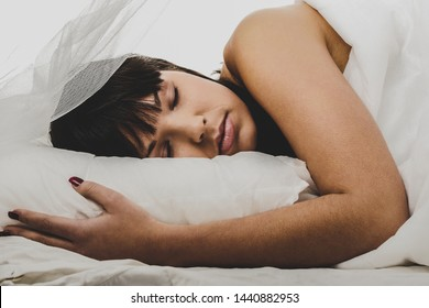 Beautiful young mixed race woman lying on pillow with closed eyes.