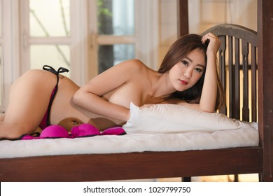 beautiful young model asian nude posed sexy in purple underwear on the white bedroom