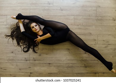 Beautiful young model ballet dancer lying on floor. Top view. working out at home studio, doing yoga exercise. Female, long curly brunette hair, a luxurious figure. dark tights . twine.