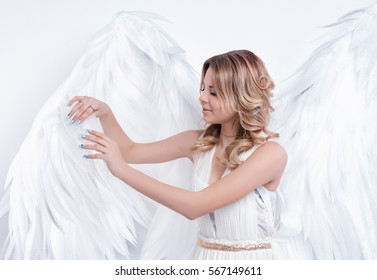 beautiful young model with big angel wings posing in the studio. white background