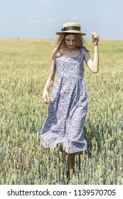 Beautiful young model in the field among the ears. The girl is blonde in a beautiful dress and cute hat
