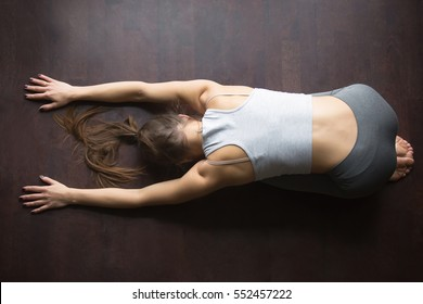 Beautiful young model girl working out at home, doing yoga exercise for spine on wooden floor, lying in Child Pose, Balasana Posture, resting after practice. Full length, high angle view