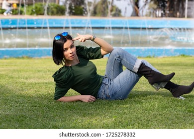 Beautiful young model lying on the grass at the park while making a gun gesture with her hand, amazing water fountain in the background