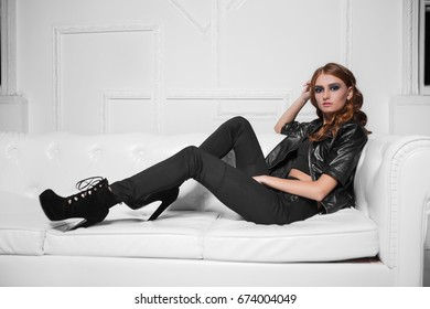 Beautiful young model lying on the sofa in black fashionable clothes