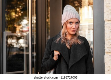 beautiful young model in pink knitted hat standing do to work, on background mirrow wall on  sunny autumn day in  big city. Autumn warm photo.Woman smiling and look away, joyful cheerful mood.