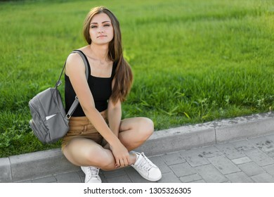 Beautiful young model posing for the camera sitting on the curb in the street.