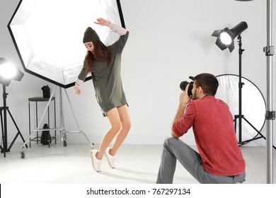 Beautiful young model posing for professional photographer in studio