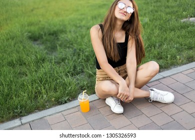 Beautiful young model posing with smoothies for the camera sitting on the street.