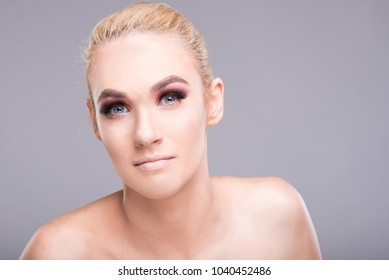 Beautiful young model posing wearing professional make-up looking at camera on black background with copyspace advertising area