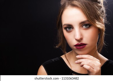 Beautiful young model with professional perfect elegant makeup and a coiffure made by stylists in a beauty salon touching her chin by a hand. free space for text