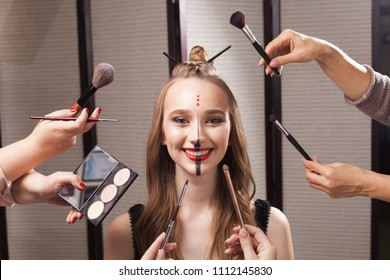 Beautiful young model with professional unusual makeup and a coiffure with topknot and braid made by stylists in a beauty salon is surrounded by hands holding brushes and palette.
