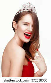 Beautiful young model in red dress  posing in the studio on a white background