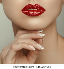 Beautiful young model with red lips and french manicure. Part of female face with red lips. Close-up of woman lips with glossy red lipstick. Glamour red lips make-up, purity skin. Retro beauty style