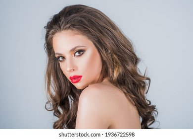 Beautiful young model with red lips, smokey eyes and nude shoulders