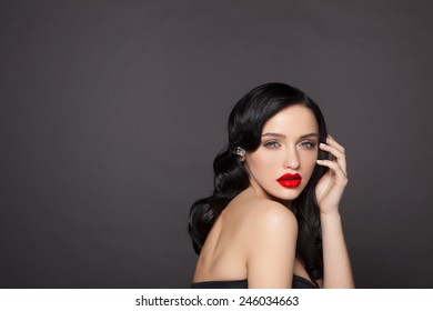 Beautiful young model with red lips and white manicure,curly hair,hairdressing,hand at the person