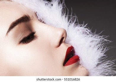 Beautiful young model with red lips, white fur in face, fashion style, beauty style