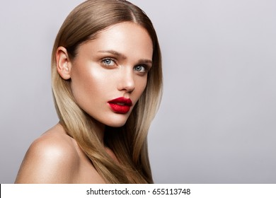 Beautiful young model with red lips and nude manicure