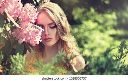 Beautiful young model spring girl   in flowers with hairstyle in summer blossom park. Woman in a blooming garden . Fashion, Cosmetics & Perfumes