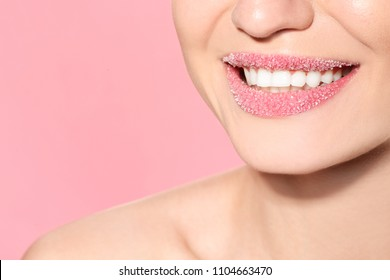 Beautiful young model with sugar lips on color background
