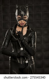 Beautiful young model wearing hand made cat costume in front of black wall.