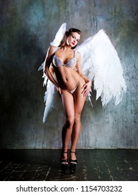 beautiful young model wearing white angel wings in the studio