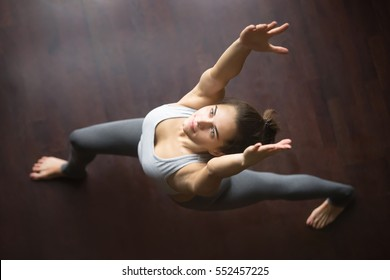 Beautiful young model working out in home interior, doing yoga exercise on wooden floor, standing in warrior I, virabhadrasana 1 pose. Top view. Full length