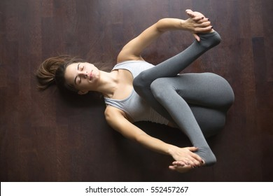Beautiful young model working out at home, doing yoga exercise on floor, lying in Supta Gomukhanasa (reclined cowface pose), posture for sciatica, resting after practice. Full length, high angle view