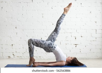Beautiful young model working out in loft interior, doing stretching yoga exercise on mat, eka pada setu bandha sarvangasana pose, glute bridge. Sport active lifestyle concept. Full length, side view
