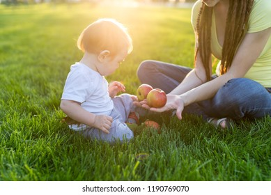 Beautiful young modern mom playing with her cute baby son counting apples in a Sunny Park. The Concept child education