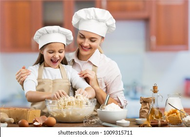 Beautiful young mom and child cookingd